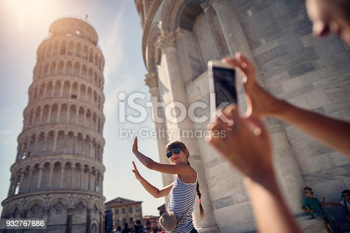 Family sightseeing Pisa, Italy. Teenage girl is posing by the leaning tower of Pisa.  Mother is taking photos and the bored boys are fighting in the background. Kids are aged 8 and 11. Nikon D810