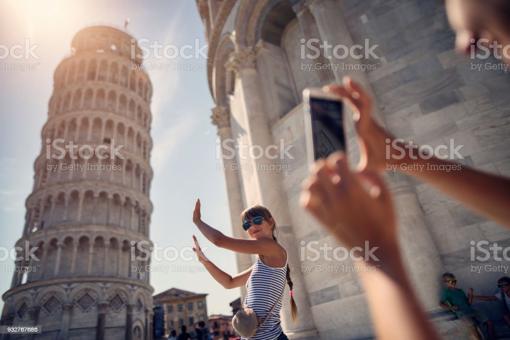 holding up photos of the Leaning Tower of Pisa stock photo