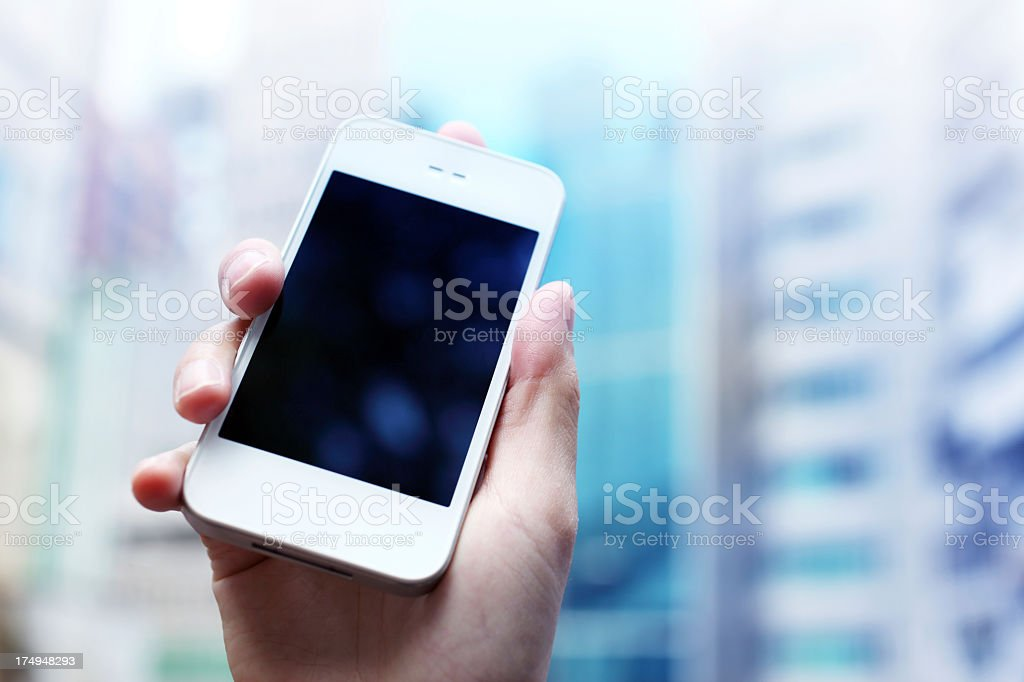 Holding Up Smart Phone Close-up of on female hands holding up a smart phone, in a city background. Adult Stock Photo