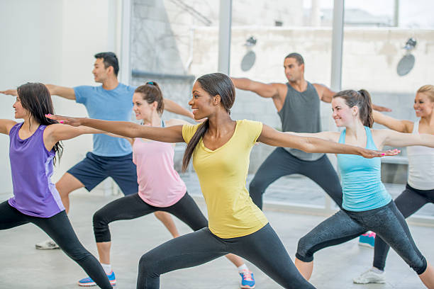 Holding Warrior Two Pose in Yoga A multi-ethnic group of young adults are taking a yoga class together and are holding warrior two pose. yoga class stock pictures, royalty-free photos & images