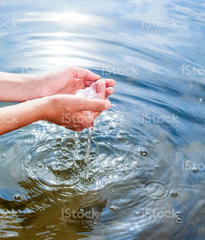 Holding water in cupped hands stock photo