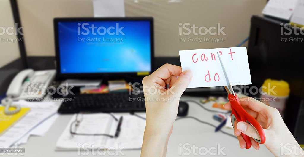holds card with text can't do on messy desk royalty-free stock photo