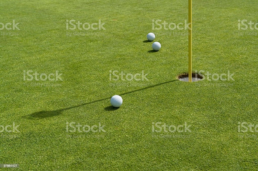 hole and golf balls in sunny ambiance royalty-free stock photo
