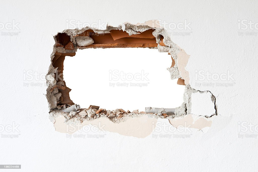A hole in a brick wall surrounded by white stock photo
