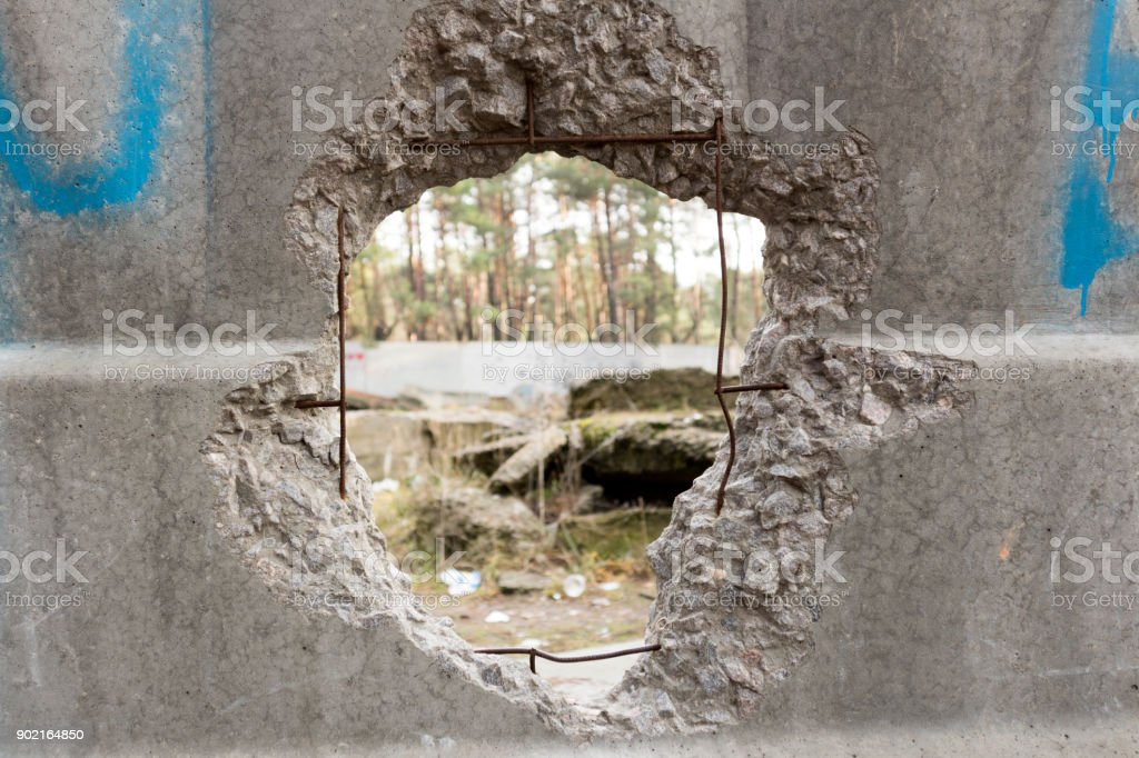 Hole in a concrete fence overlooking the pine forest stock photo