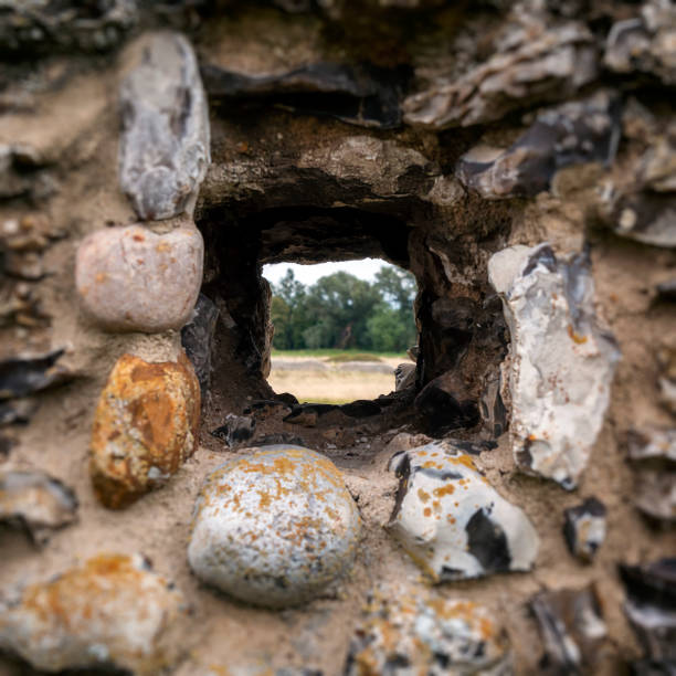 Hole in a flint-stone wall stock photo