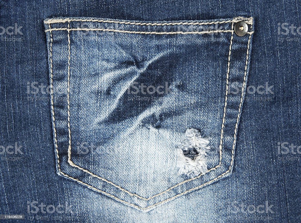 Hole in a pocket of old jeans royalty-free stock photo