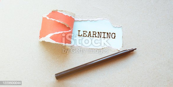 472273278 istock photo Hole in a sheet of red paper on a red background. Mock up with torn paper LEARNING text. 1223500044