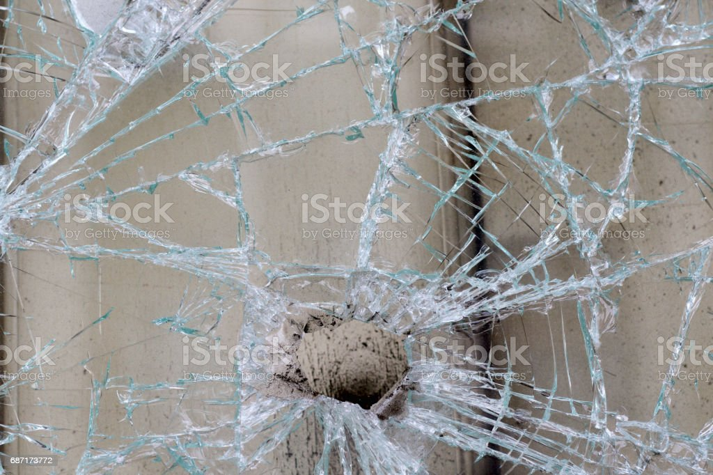 Hole in crazed cracked glass in London city window stock photo