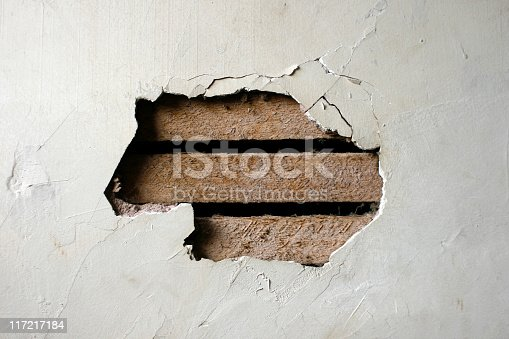 Closeup of a hole in a plaster wall.
