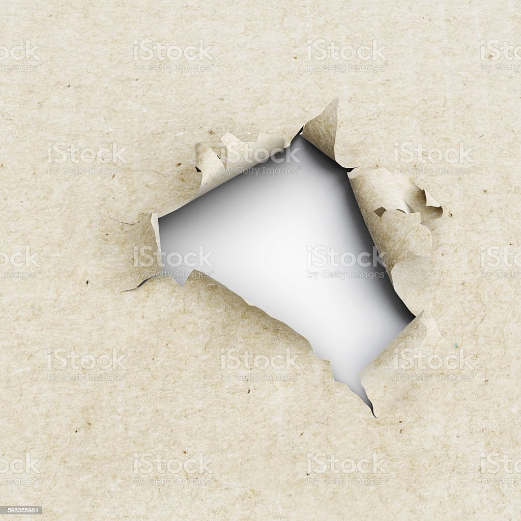 Hole in the kraft paper on a white background. royalty-free stock photo