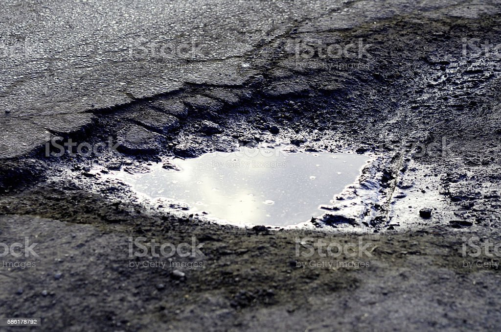 Hole in the road filled with water stock photo
