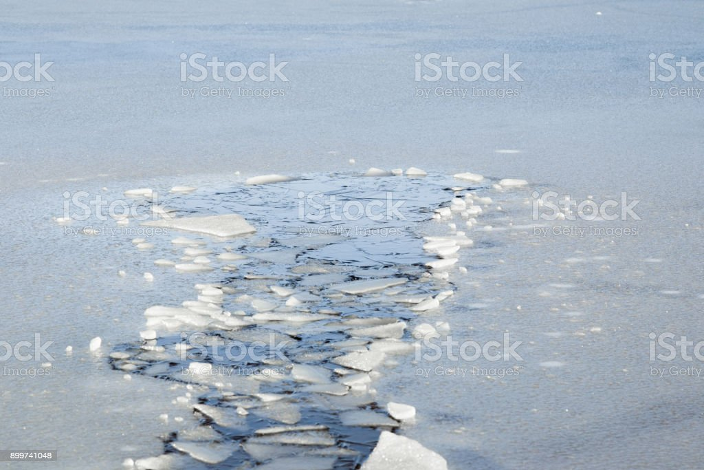 Hole in the thin ice. Someone fell through the ice. Dangerous concept. Freezing and melting time for ice on the water reservoirs in winter. stock photo