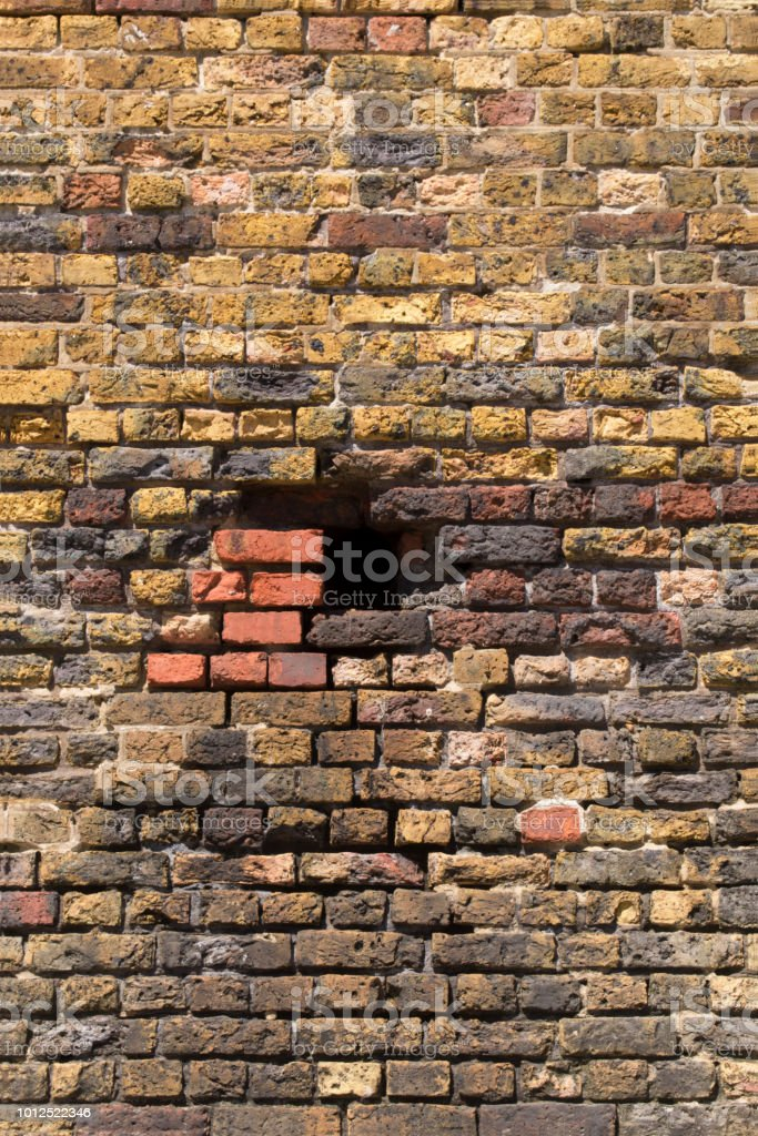 An old brick wall with a square hole in it.