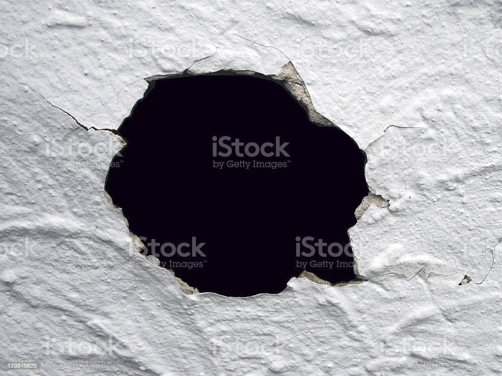 Hole and cracks in a wall pattern.
