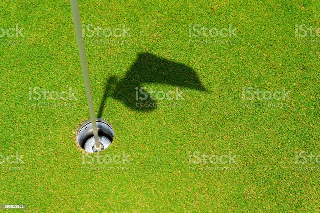 hole on putting green with flag stick and shadow of flag. hole or...