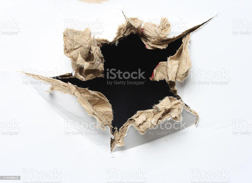 Hole poked through white carton stock photo