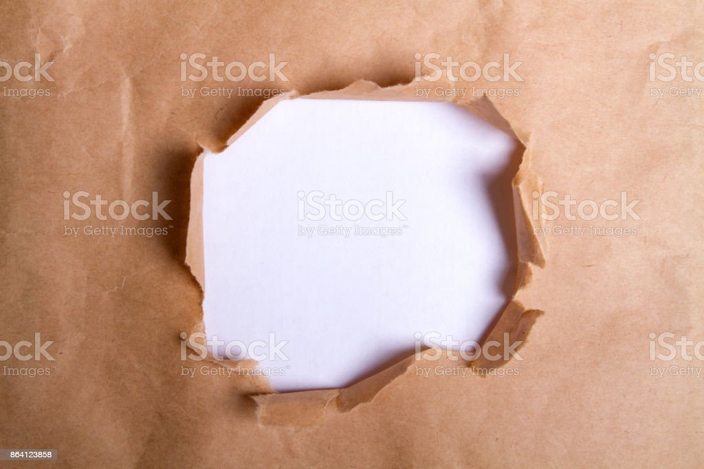 Hole ripped in brown paper royalty-free stock photo