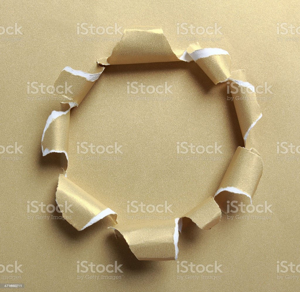 Hole ripped in gold paper royalty-free stock photo