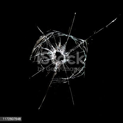 hole with cracks in the glass isolated on a black background