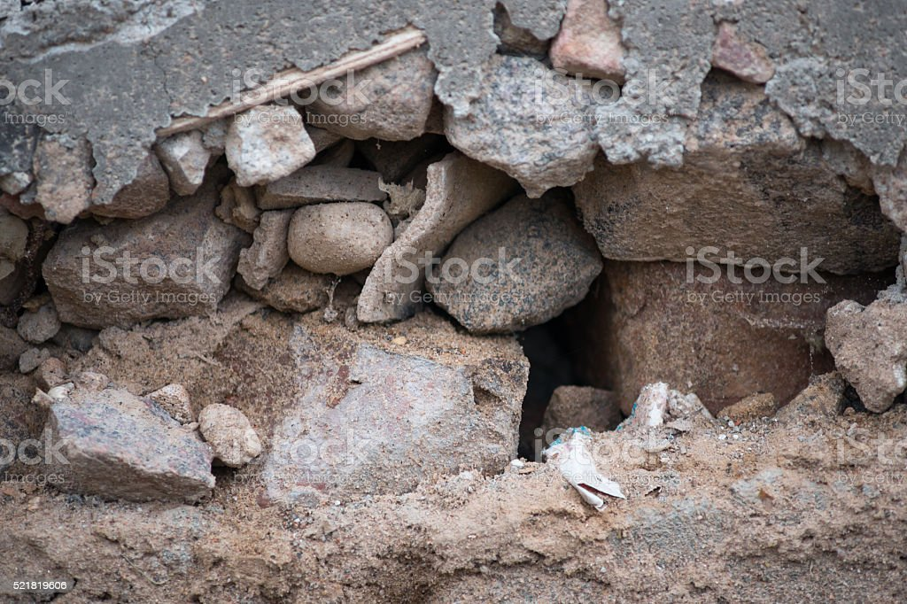 Hole with debris, stones and wood stock photo