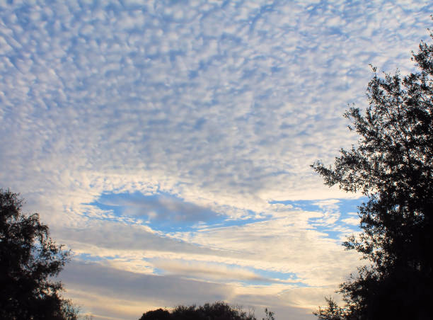 Holes form in the sky at sunrise stock photo