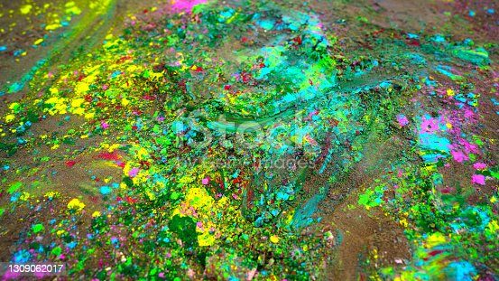 istock Holi colors and rangoli scattering on ground. Holi color powders closeup with herbal flower rose dye. 1309062017