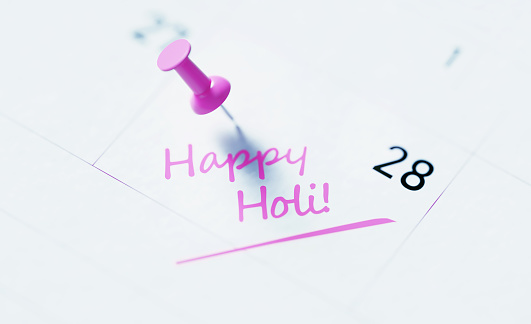 Holi Concept - Happy Holi Note Pinned By A Pink Thumbtack On A White Calendar