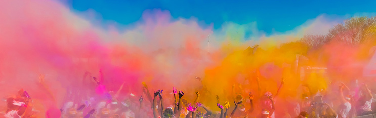 Crowd throwing bright coloured powder paint in the air, Holi Festival Dahan