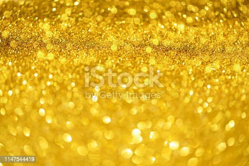 881350776 istock photo Holiday abstract texture. Christmas card with copy space. Gold bokeh background, defocused lights. 1147544419