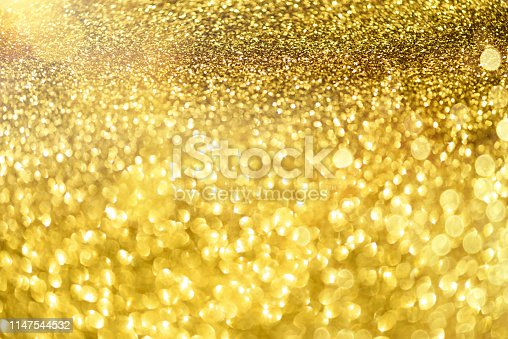 881350776 istock photo Holiday abstract texture. Christmas card with copy space. Gold bokeh background, defocused lights. 1147544532