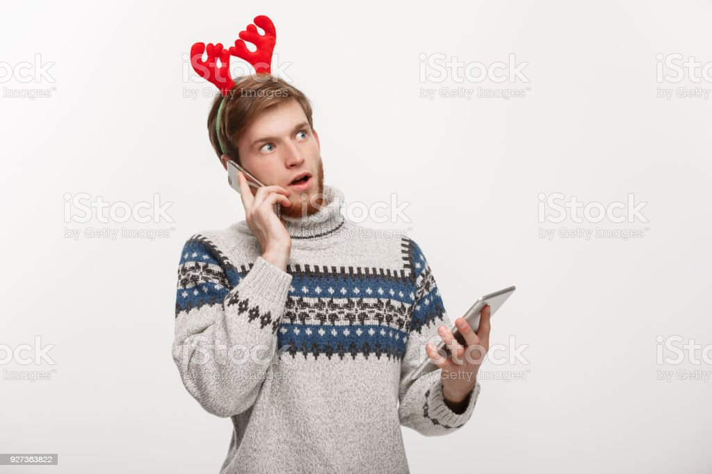 Holiday and Business Concept - Young handsome man busy working on phone and digital tablet. - Royalty-free Adult Stock Photo