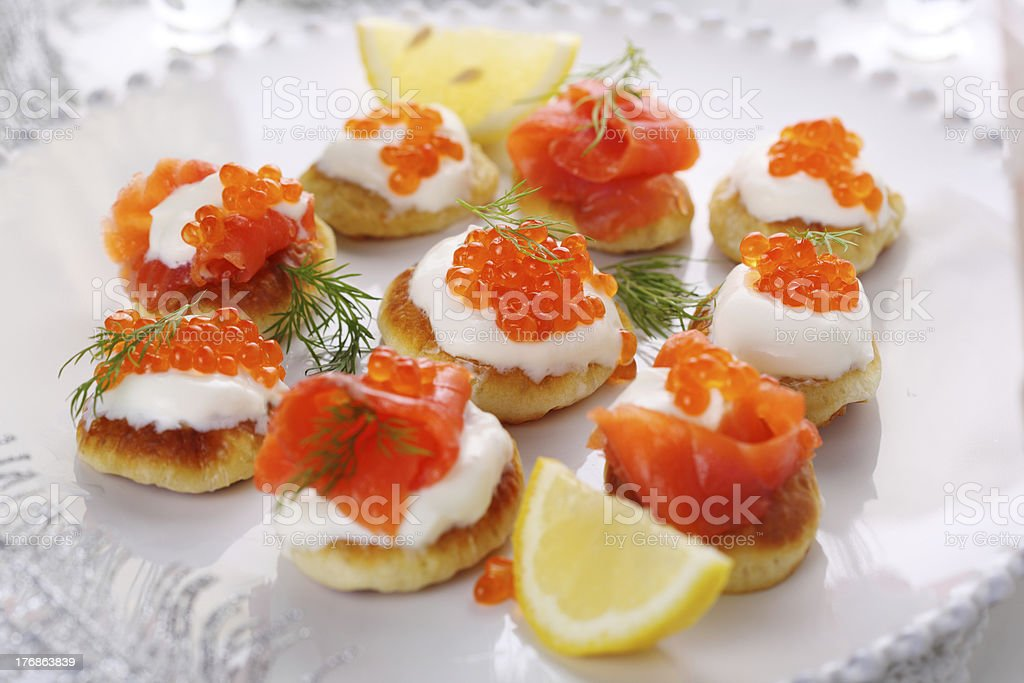 Holiday appetizer with caviar and salmon on white plate, royalty-free stock photo