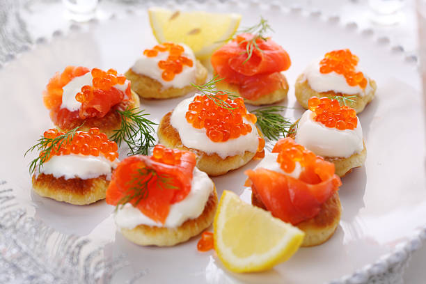 Holiday appetizer with caviar and salmon on white plate, stock photo