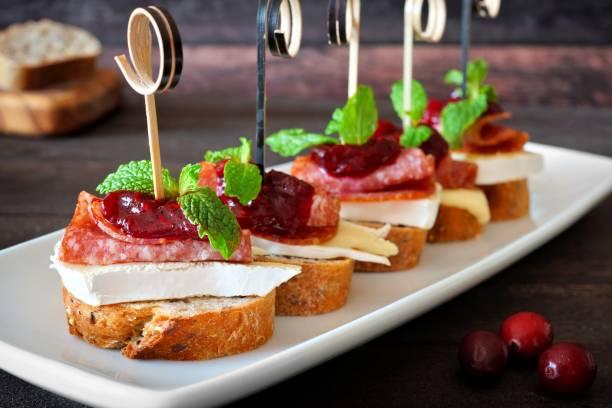 urlaub vorspeisen mit cranberry-sauce auf einem weißen teller - salami vorspeise stock-fotos und bilder