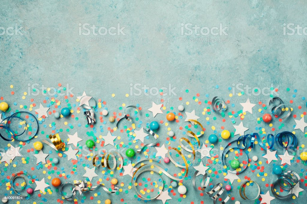 Holiday background decorated colorful confetti, star, candy and streamer on blue vintage table top view. Flat lay style.