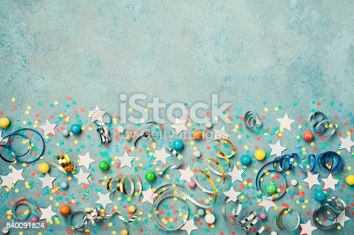 istock Holiday background decorated colorful confetti, star, candy and streamer on blue vintage table top view. Flat lay style. 840091824