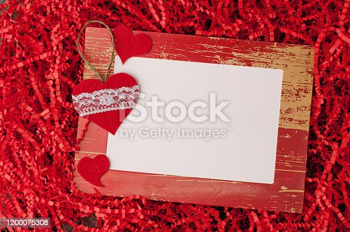 914465180 istock photo Holiday background for Valentine's Day on a gray cement background with red cut paper for packaging and hearts, gifts and stickers for congratulation text. 1200075308