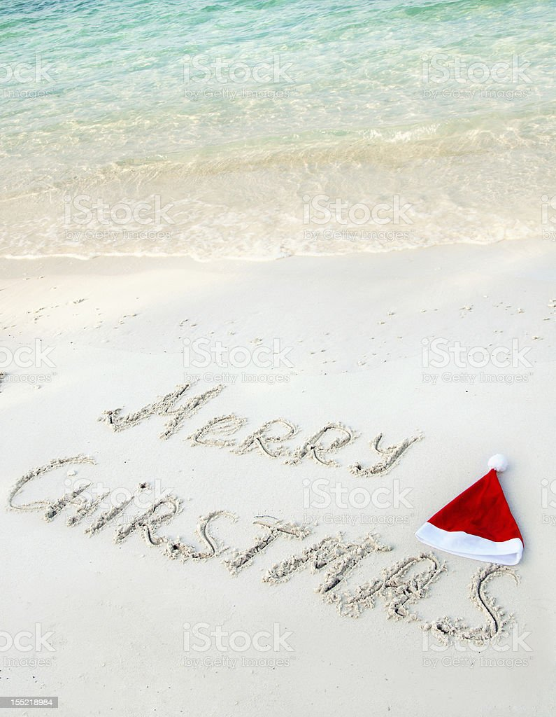 Holiday background - Merry Christmas written on tropical beach sand royalty-free stock photo