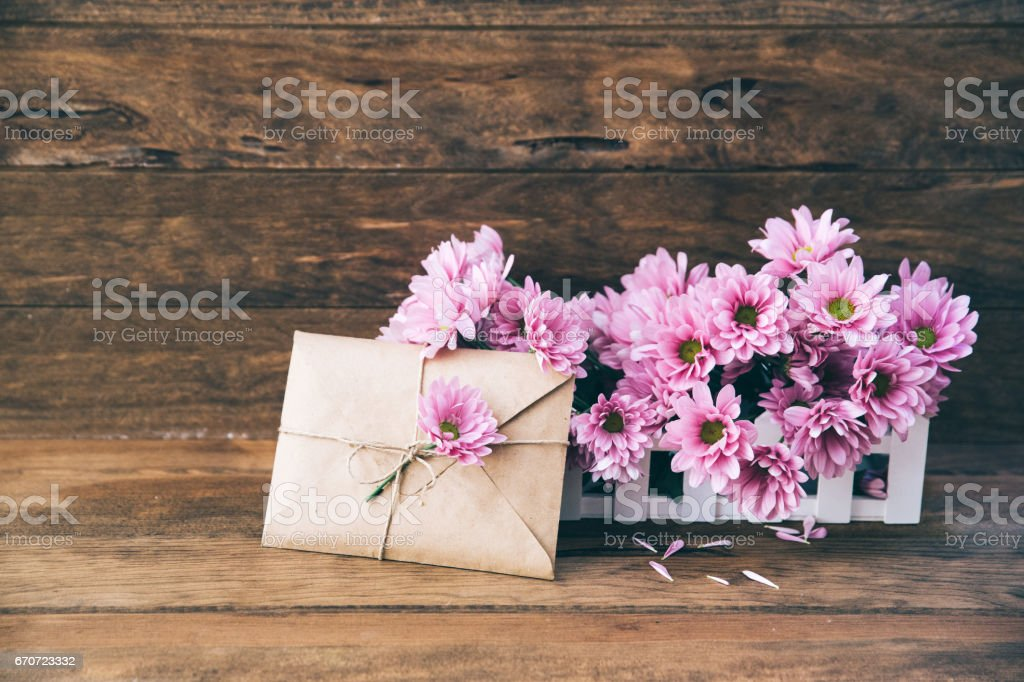 Holiday background with garden flowers and craft envelope on wooden table - foto de stock