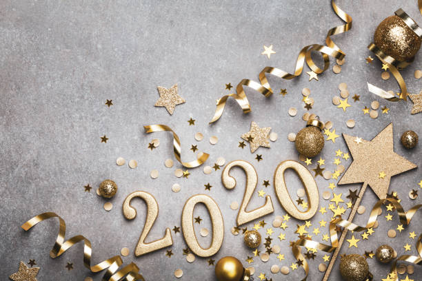 holiday background with golden christmas decorations and new year 2020 numbers and confetti stars top view. - new year imagens e fotografias de stock
