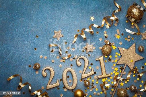 istock Holiday background with golden Christmas decorations and New year 2021 numbers and confetti top view. 1277173008