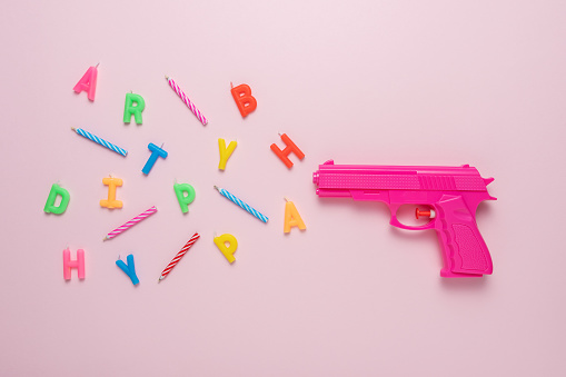 Holiday background with pink gun and birthday candles. Minimal creative concept.