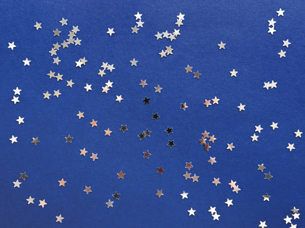 Holiday background with silver star confetti on blue background. Good backdrop for Christmas and New Year cards. stock photo