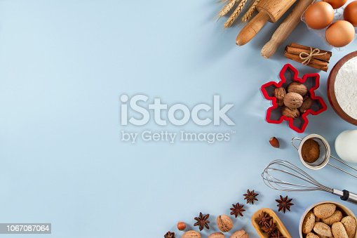 Holiday baking ingredients in frame composition on soft blue background