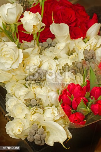 Red and white roses with tulips and grey florals make up this festive arrangement.