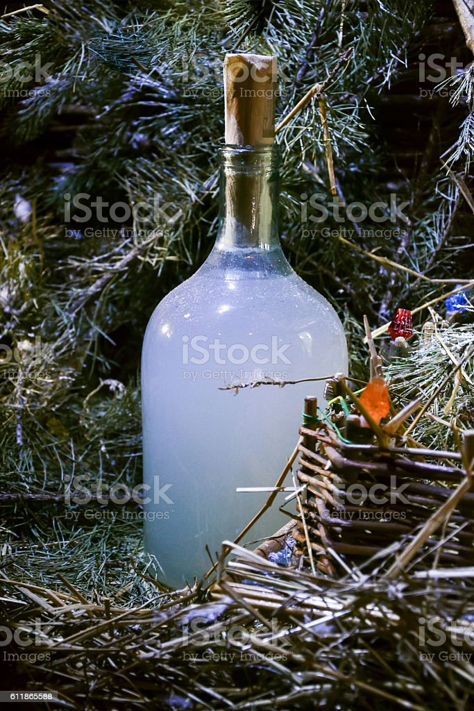 Holiday bottle of homemade strong drink hooch near Christmas tree stock photo