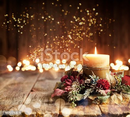 Christmas holiday elegant candle set against Christmas lights and old textured and toned wood background