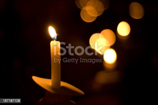 This was taken at a church for a holiday service called Carols and Candles. The flame from the candle represents the light of Jesus Christ in a dark and evil world. This photo would be great for a candlelight vigil also or for a design for mourning or memorial.