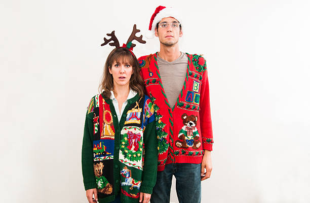 Holiday cheer. A young couple in ugly Christmas sweaters stand and look totally unimpressed. Horizontal image with copy space. ugliness stock pictures, royalty-free photos & images